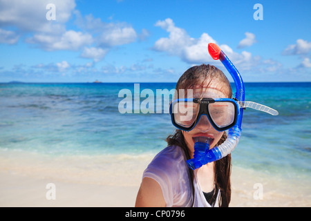 Young girl with dive mask and snorkel standing on the shore of Anse Patates on La Digue in the Seychelles - Stock Photo