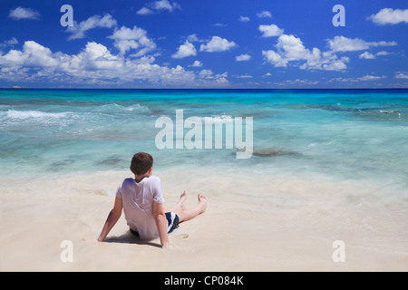 A young boy sitting in the tropical waters of Anse Patates on La Digue in the Seychelles - Stock Photo