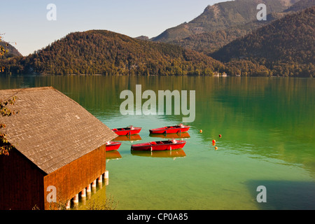 red boats and a boathouse on Wolfgangsee lake in Austria - Stock Photo
