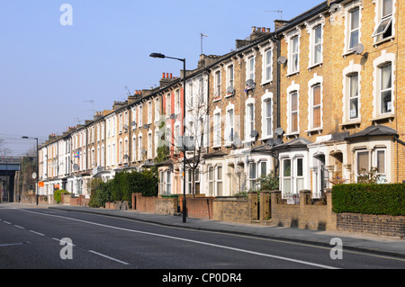 Long row of old three storey terraced flats & apartments without parked cars in Hackney London close to town centre - Stock Photo