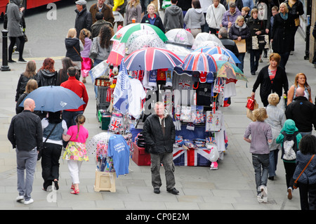 View from above looking down Chester crowded shopping street stall selling umbrellas & souvenirs on busy starting - Stock Photo