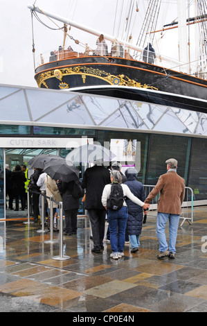 Restored Cutty Sark tourist attraction with tourists queuing in the rain under umbrellas - Stock Photo