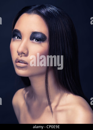 Artistic beauty portrait of an asian woman with sparkling black eyeshadows isolated on dark background - Stock Photo