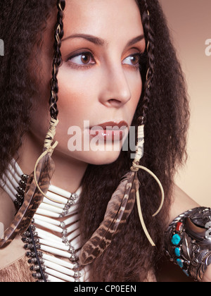 Artistic beauty portrait of a beautiful woman wearing aboriginal native accessories and feathers in her hair - Stock Photo