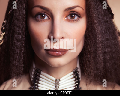 Closeup beauty face portrait of a beautiful woman wearing native accessories - Stock Photo