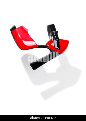 Trendy red with black high heel platform shoe falling through the air isolated on white background - Stock Photo