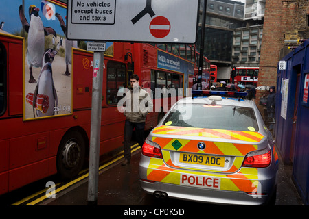 A Metropolitan police car drives carefully past pedestrians and stationary traffic during a central London emergency. - Stock Photo