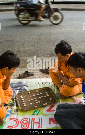 Vertical close up of Vietnamese men playing cờ tướng, a popular chess-like game in Asia, on the side of the road. - Stock Photo