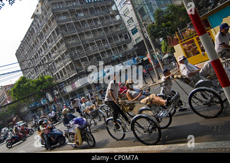 Horizontal view of cycle rickshaws carrying Western tourists wearing protective face masks on the streets of Ho - Stock Photo