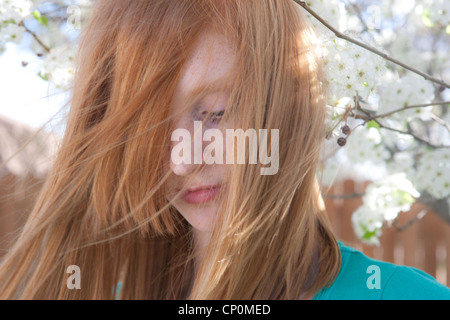Red haired teenage girl looks down with hair flowing in front of her face, white blossoms in the background. - Stock Photo