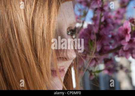 profile of woman with red hair and cherry blossoms in background. - Stock Photo