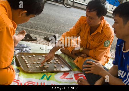 Horizontal close up of Vietnamese men playing cờ tướng, a popular chess-like game in Asia, on the side of the road. - Stock Photo