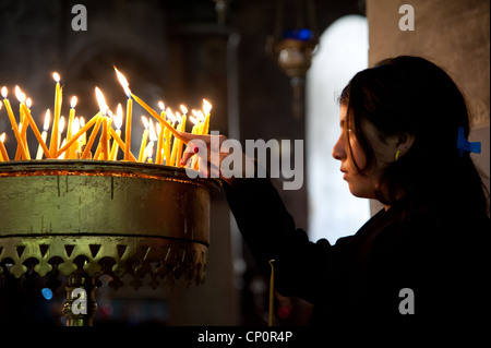 A girl lights a prayer candle in the Church of the Nativity, traditional site of the birth of Jesus Christ. - Stock Photo