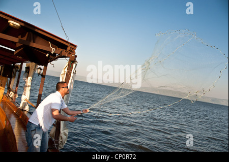 An Israeli boat pilot demonstrates casting a fishing net on the Sea of Galilee. - Stock Photo