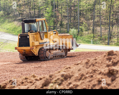 Land being levelled and cleared by yellow earth moving digger - Stock Photo