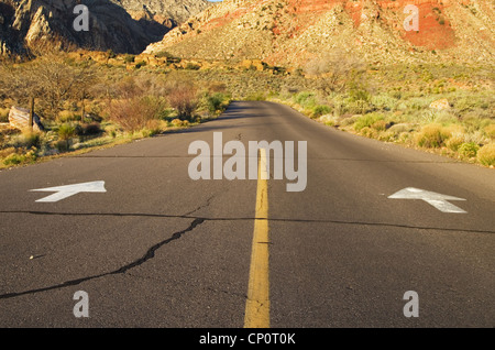 arrows on a one way road point forward towards the mountains - Stock Photo