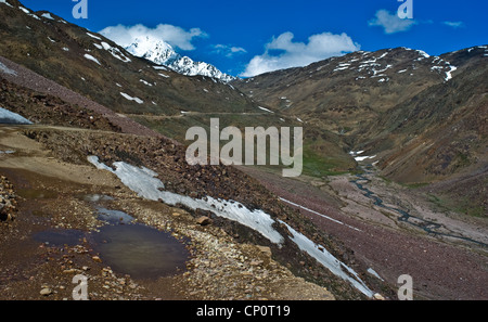 Gravel road to Chandra Taal lake (Moon lake) in early summer, still officially closed - Stock Photo