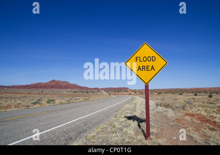 horizontal image of flood area sign and road in the Utah desert - Stock Photo