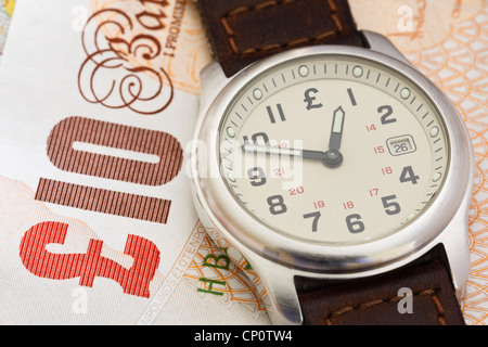 Wristwatch clock on a Sterling ten pound note GBP to illustrate time to put money in a pension concept. England, - Stock Photo