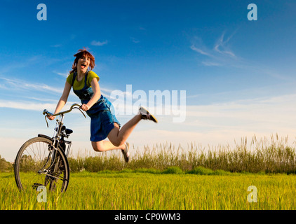 Happy woman with a old bicycle in a green meadow and jumping - Stock Photo