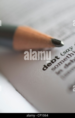 Debt the word debt in dictionary with pencil - Stock Photo