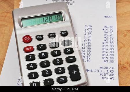 Ein Taschenrechner liegt auf einer Rechnung | A pocket calculator lies on an invoice. Stock Photo