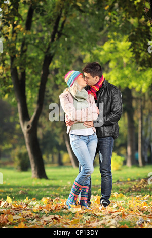 A loving couple kissing in the park in autumn - Stock Photo