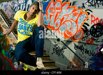 A young african american man rnb music fan posing in front of wall with graffiti with - Stock Photo