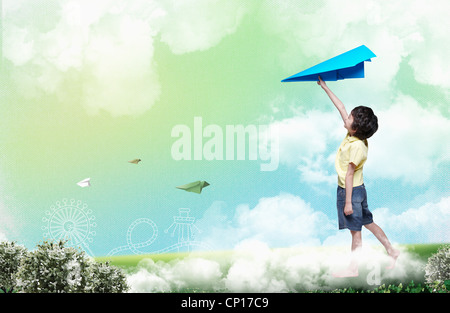 A boy holding up blue paper plane - Stock Photo