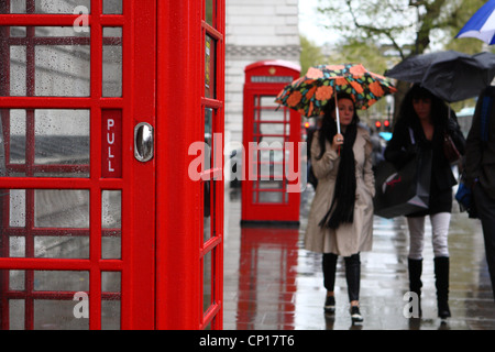 people walking in the rain passed red telephone boxes - Stock Photo