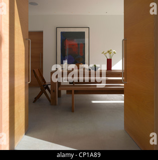 Pond and Park House, Dulwich, London. View of white-walled dining room through modern pale wood double doors - Stock Photo
