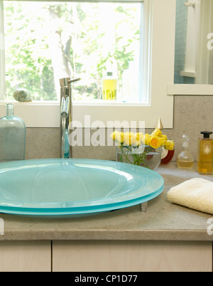 Blue glass washbasin set on marble topped unit in contemporary bathroom - Stock Photo