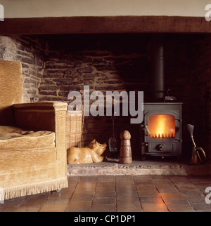 Upholstered sofa in front of woodburning stove in inglenook fireplace - Stock Photo