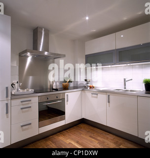 A modern white kitchen with white units, stainless steel integral oven and extractor fan, wooden floor - Stock Photo