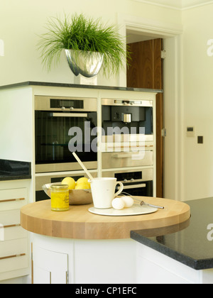 Cooking ingredients on wooden worktop in contemporary kitchen - Stock Photo