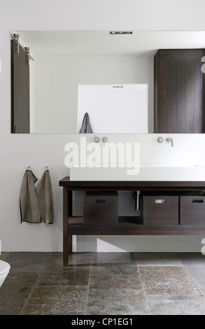 Pair of washbasins set on wooden cupboard unit in modern bathroom - Stock Photo