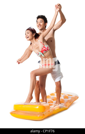 Young man and young woman in swimsuit having fun in air bed - Stock Photo