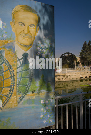 Hafez al Assad Poster In Front Of The Norias of Bechriyyat, Hama, Syria - Stock Photo