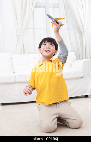Little boy playing toy plane - Stock Photo
