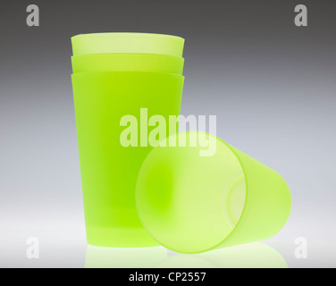 Four green plastic beakers - Stock Photo