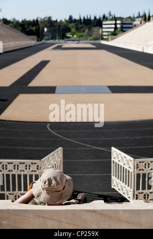 Tourist sit in the stands of the Panathenaic stadium and listen the audio tour. Athens, Greece. - Stock Photo