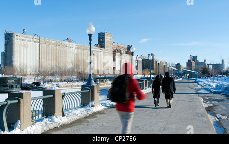 People strolling along the quays of Montreal old port. Grain elevator number 5 on the left. - Stock Photo