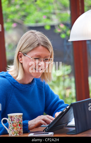 Blond woman relaxing at home in garden conservatory using her tablet iPad computer in its protective leather stand - Stock Photo