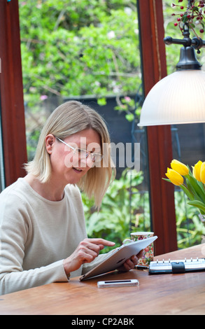 Blond woman relaxing at home in garden conservatory using her iPad tablet computer - Stock Photo