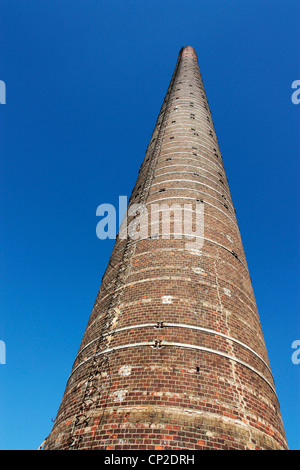 industrial tall brick chimney against blue sky - Stock Photo