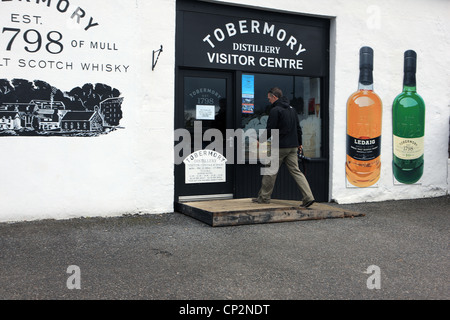 Man walking towards the Tobermory Distillery Centre in Tobermory on the Isle of Mull - Stock Photo