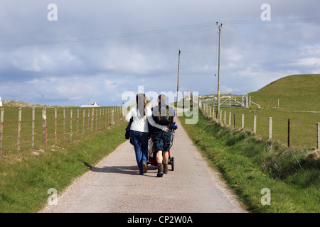 Young family enjoying a walk in the countryside pushing a pram - Stock Photo