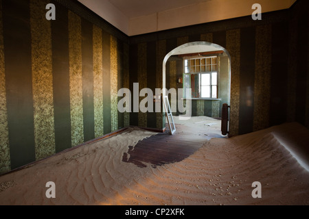 Sand-covered floor in a room in Kolmanskop - Stock Photo