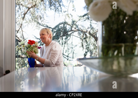 Senior caucasian woman with bunch of flowers in living room at home - Stock Photo
