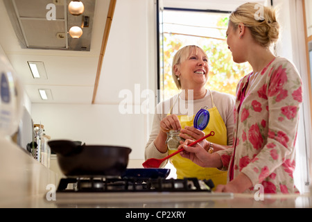 Happy mother and daughter having fun while preparing food and cooking together in kitchen at home - Stock Photo